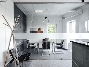 Wnętrze biurowe z okładziną z paneli betonowych na ścianach.