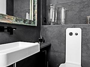 Łazienka z wykorzystaniem ciemnych płyt betonowych.