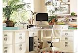białe biurko narożne, biały fotel z drewna, dywan w kolorowe trojkąty