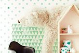 biała ściana w zielone kropki, czarny fotel, regał domek, duży pluszowy miś