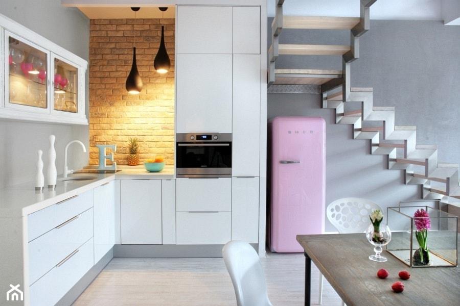 białe meble kuchenne z białym blatem, różowa lodówka, czerwona cegła, białe krzesło z tworzywa