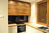 białe szafki kuchenne z drewnianym blatem