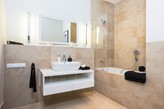 beżowe płytki łazienkowe, lustro bez ramy, biała szafka łazienkowa