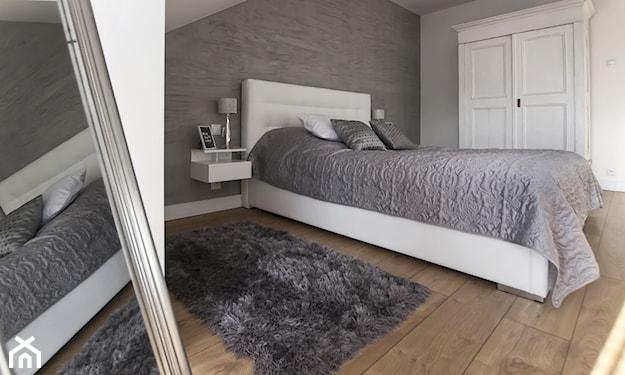 nowoczesna sypialnia, drewniana podłoga, szary dywan z długim włosiem, szara narzuta, biała rama łóżka