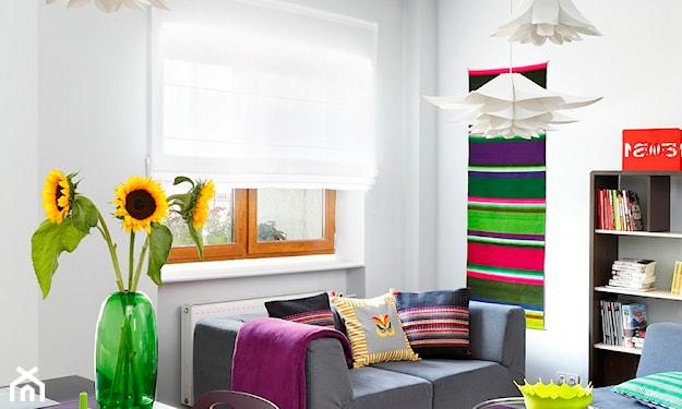 szara sofa, słoneczniki w zielonym wazonie, białe lampy wiszące, okrągłe stoliki, fioletowa narzuta, biała roleta rzymska