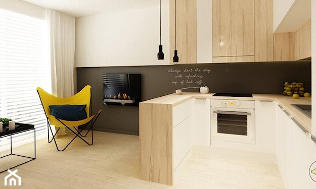 żółty fotel, czarna lampa wisząca, farba tablicowa, białe meble kuchenne z drewnianym blatem