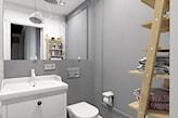 mała łazienka w szarościach, lustro bez ramy, drewniana drabina, białe szafki łazienkowe
