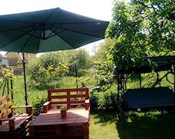 Średni ogród za domem z parasolem z huśtawką, styl nowoczesny - zdjęcie od Karolina Krysiak