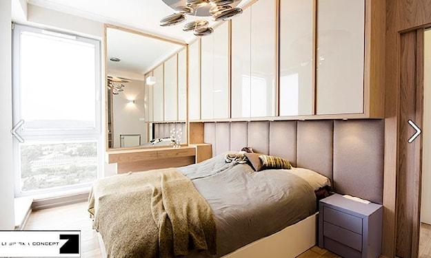 białe szafki z połyskiem nad łóżkiem, beżowa narzuta, szara szafka nocna