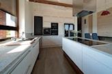 białe meble kuchenne, drewniana podłoga, metalowy okap, kuchnia z wyspą