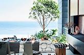 taras z widokiem na morze, szare krzesła, drewniany taboret, biały obrus w okręgi