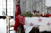 drewniana podłoga, biały obrus w czerwone gwiazdy, drewniane panele ścienne