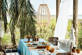 wiklinowa ozdoba nad stołem, obrus z biało-turkusowe pasy, wiklinowe krzesła