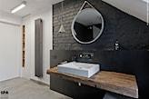 łazienka w stylu industrialnym, szara cegła, okrągłe lustro, drewniany blat podumywalkowy, bateria ścienna