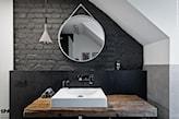łazienka w stylu industrialnym na poddaszu, okrągłe lustro łazienkowe, drewniany blat, szara cegła