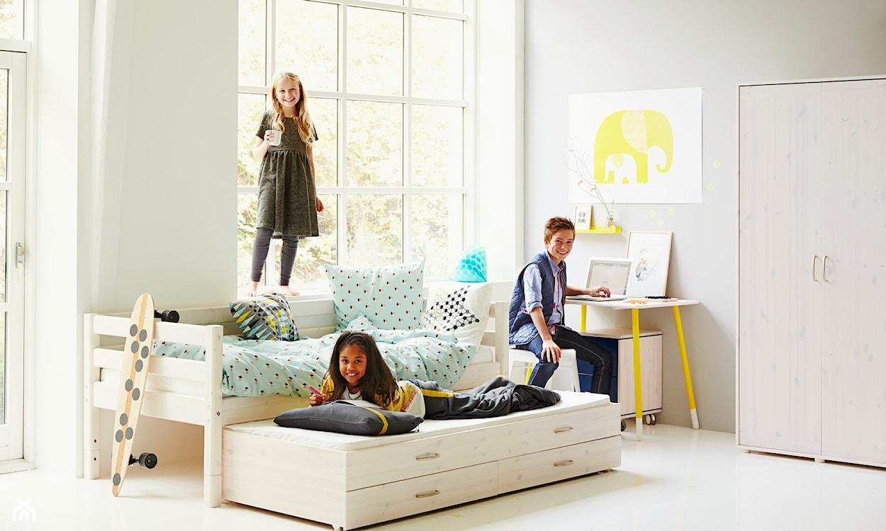 łóżko wysuwane, żółte biurko, drewniana szafa, grafika ze słoniem, deskorolka
