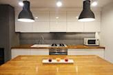 białe meble kuchenne z drewnianym blatem, szara lampa wisząca, szare ściany w kuchni, kuchnia w stylu skandynawskim