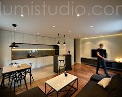 MIESZKANIE W BLOKU - zdjęcia z realizacji-nowe szaty 30 metrowej strefy dziennej - Średni biały czarny salon z barkiem z kuchnią z jadalnią, styl minimalistyczny - zdjęcie od ILLUMISTUDIO