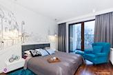 niebieski fotel, drewniana podłoga, szare zasłony, czarno-biała grafika nad łóżkiem