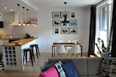 stół na metalowych nogach, szara sofa, metalowe hokery, drewniana pdołoga