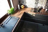 czarne meble kuchenne z drewnianym blatem, świeże zioła w doniczkach
