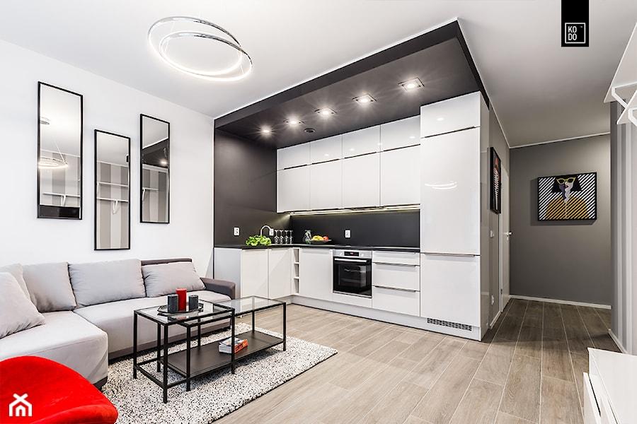 GEOMETRIA KONTROLOWANA - Średnia otwarta biała czarna kuchnia w kształcie litery l w aneksie, styl nowoczesny - zdjęcie od KODO projekty i realizacje wnętrz