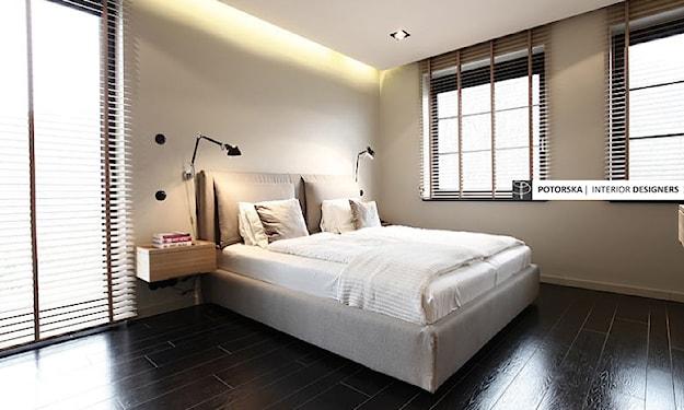 beżowe łóżko, biała pościel, żaluzje wewnętrzne, podłoga z ciemnego drewna