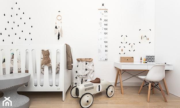 drewniana podłoga, białe biurko, białe ściany w czarne kropki, zabawkowy samochód retro