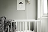 szare ściany w pokoju dziecka, szara narzuta, białe łóżeczko dziecięce, ozdobny ptak nad łóżeczkiem