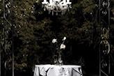 kryształowy żyrandol, metalowa brama, szary obrus
