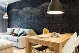 czarny kamień dekoracyjny w salonie, drewniany stół jadalniany, białe krzesła na drewnianych nogach