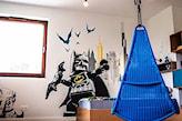 kobaltowy fotel wiszący, naklejka ścienna z animowanym batmanem, białe meble w pokoju dziecka