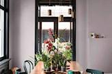 lawendowe ściany w jadalni i zielone krzesła
