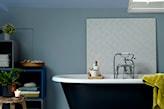 niebieskie ściany i wolnostojąca wanna w łazience