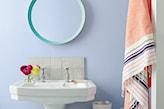 niebieskie ściany i biała umywalka w łazience