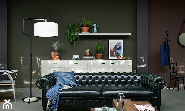 ciemne ściany, czarna sofa, biała lampa podłogowa