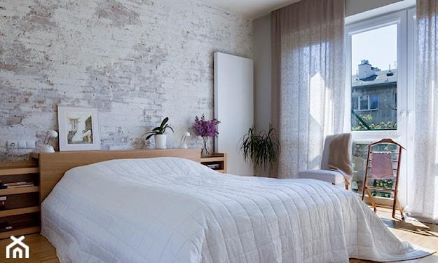 biała narzuta, drewniana podłoga, ściana z białej cegły, szara firana
