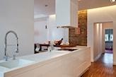 biała kuchnia, drewniana podłoga, ceglana ściana, drewniany stół