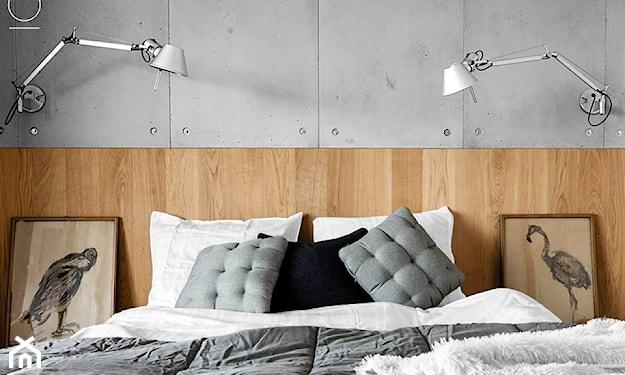 biała pościel, szare poduszki, biała narzuta z długim włosiem, betonowe płyty na ścianie w sypialni