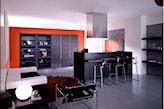 pomarańczowa ściana, grafitowe meble, metalowe hokery