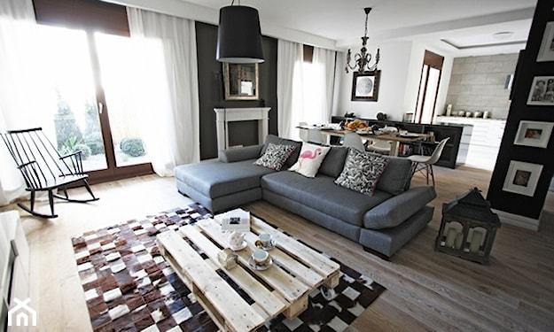 szara sofa narożna, stolik z palet, biały kominek, lampa wisząca z czarnym abażurem, białe długie zasłony