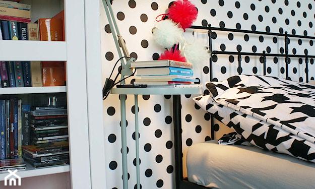 czarna metalowa rama łóżka, metalowa szafka nocna z lampą, biała tapeta w czarne kropki