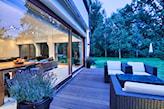 drewniane deski tarasowe, ratanowe meble ogrodowe, zielony ogród przed domem