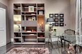 szklane biurko, lampa stołowa z bezowym abażurem, biały regał, beżowy puszysty dywan