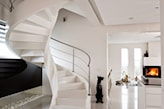 biała kamienna podłoga, białe spiralne schody, metalowa balustrada, kominek w salonie