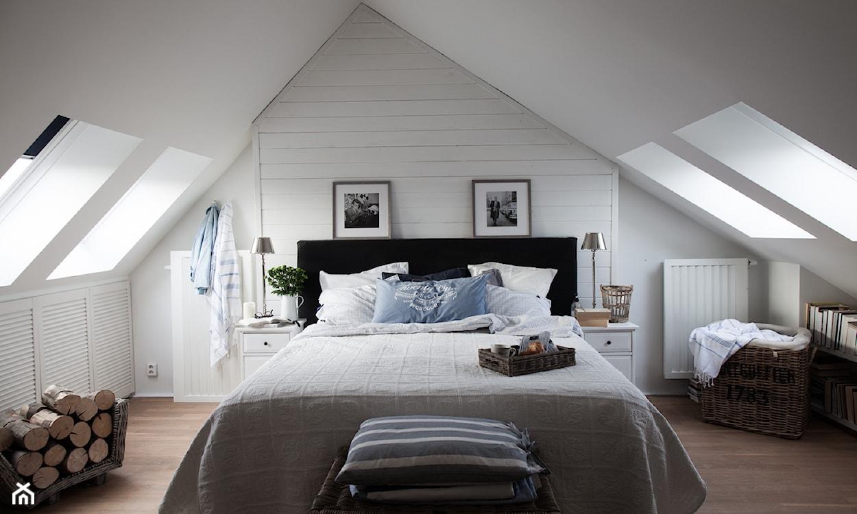 sypialnia na poddaszu, szara narzuta, poduszka w pasy, kosz z plecionki, metalowa lampa stołowa, białe szafki nocne