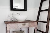 drewniana drabina w łazience, różowa szafka pod umywalką, lustro z czarną ramą