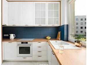 Białe meble do kuchni z elementami w kolorze drewna
