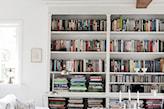 biały regał z książkami, biała sofa, srebrny świecznik