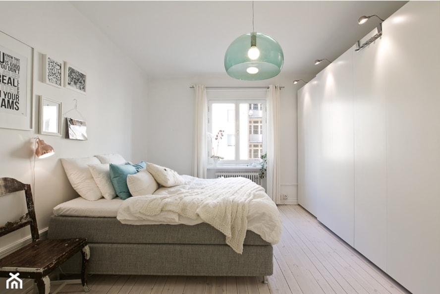 lampa wisząca z zielonego szkła, białe zasłony, biała pościel, miedziana lampa ścienna, szare łóżko